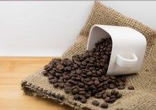 Chicchi di caffè in tazza di caffè Immagine Stock