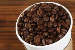 Chicchi di caffè in tazza di carta Immagine Stock
