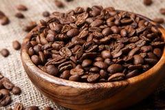 Chicchi di caffè in un piatto di legno Fotografia Stock