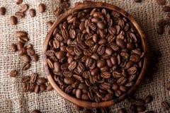 Chicchi di caffè in un piatto di legno Immagine Stock