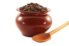 Chicchi di caffè in un vaso con un cucchiaio di legno Immagini Stock Libere da Diritti