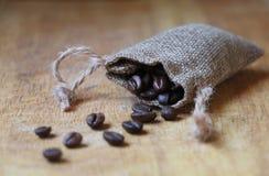 Chicchi di caffè in una borsa della tela immagini stock