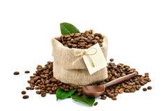Chicchi di caffè in una borsa di tela di sacco su un fondo bianco con l'etichetta in bianco fotografie stock libere da diritti