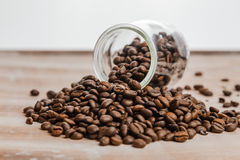 Chicchi di caffè in una bottiglia di vetro su fondo di legno Fotografie Stock Libere da Diritti