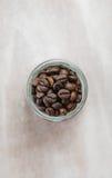 Chicchi di caffè in una bottiglia di vetro su fondo di legno Fotografia Stock