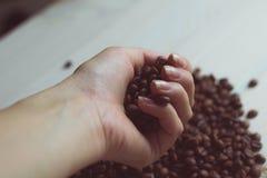 Chicchi di caffè in una mano femminile Fotografia Stock
