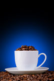 Chicchi di caffè in una tazza bianca su un fondo blu Immagini Stock