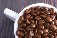 Chicchi di caffè in una tazza bianca su un fondo di legno scuro Fotografie Stock Libere da Diritti