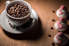 Chicchi di caffè in una tazza con alcuni amici fotografie stock