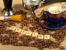 Chicchi di caffè, una tazza decorata, compressore e maniglia del gruppo con le lettere offline su un fondo della tela di iuta Fotografie Stock