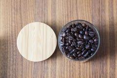 Chicchi di caffè in vetro su fondo di legno Fotografia Stock Libera da Diritti