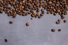 Chicchi di caff? arrostiti all'ingrosso su un fondo concreto grigio il cofee scuro ha arrostito il caff? dell'aroma di sapore del immagini stock