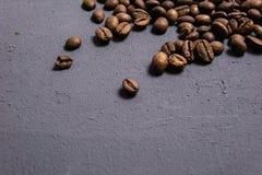 Chicchi di caff? arrostiti all'ingrosso su un fondo concreto grigio il cofee scuro ha arrostito il caff? dell'aroma di sapore del fotografie stock libere da diritti