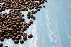 Chicchi di caff? arrostiti all'ingrosso su un fondo di legno blu il cofee scuro ha arrostito il caff? dell'aroma di sapore del gr immagine stock libera da diritti