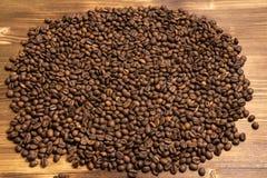 Chicchi di caff? arrostiti all'ingrosso su un fondo di legno fotografia stock