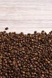 Chicchi di caff? arrostiti all'ingrosso su un fondo di legno leggero il cofee scuro ha arrostito il caff? dell'aroma di sapore de fotografie stock libere da diritti