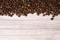 Chicchi di caff? arrostiti all'ingrosso su un fondo di legno leggero il cofee scuro ha arrostito il caff? dell'aroma di sapore de fotografia stock