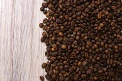 Chicchi di caff? arrostiti all'ingrosso su un fondo di legno leggero il cofee scuro ha arrostito il caff? dell'aroma di sapore de immagine stock