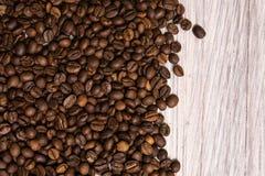 Chicchi di caff? arrostiti all'ingrosso su un fondo di legno leggero il cofee scuro ha arrostito il caff? dell'aroma di sapore de immagini stock libere da diritti