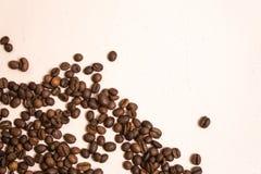 Chicchi di caff? arrostiti all'ingrosso su un fondo rosa-chiaro il cofee scuro ha arrostito il caff? dell'aroma di sapore del gra fotografie stock libere da diritti