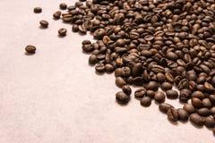 Chicchi di caff? arrostiti all'ingrosso su un fondo rosa-chiaro il cofee scuro ha arrostito il caff? dell'aroma di sapore del gra fotografia stock