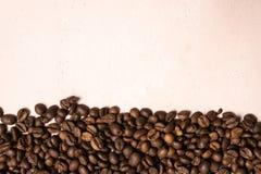 Chicchi di caff? arrostiti all'ingrosso su un fondo rosa-chiaro il cofee scuro ha arrostito il caff? dell'aroma di sapore del gra immagine stock libera da diritti