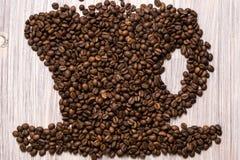 Chicchi di caff? arrostiti come una tazza su un fondo di legno immagini stock