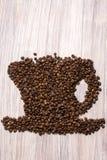 Chicchi di caff? arrostiti come una tazza su un fondo di legno immagine stock