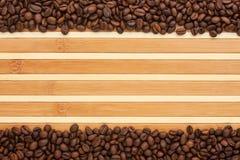 Chicchi di caffè che si trovano su una stuoia di bambù Immagine Stock