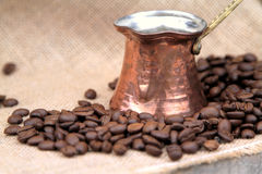 Chicchi di caffè e caffettiera di rame turca tradizionale su una tela da imballaggio Immagini Stock Libere da Diritti