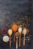 Chicchi di grano, cereali e fagioli organici crudi in cucchiai e ciotole di legno Fotografia Stock Libera da Diritti