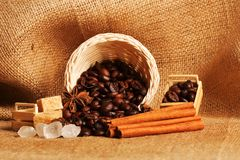 Chicchi e cannella di caffè su un fondo di tela da imballaggio Fine arrostita del fondo dei chicchi di caffè su Mucchio dei chicc Fotografia Stock Libera da Diritti