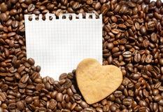 Chicchi e cuore di caffè sullo strato del blocco note Fotografia Stock Libera da Diritti