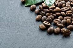 Chicchi e foglie di caffè su fondo scuro Immagini Stock Libere da Diritti
