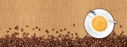 Chicchi e tazza di caffè su struttura naturale della tela da imballaggio immagini stock libere da diritti