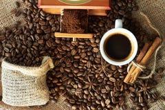 Chicchi e terra di caffè arrostiti in un macinacaffè di legno immagini stock
