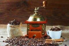 Chicchi e terra di caffè arrostiti in un macinacaffè di legno immagini stock libere da diritti