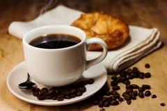 Chicco del caffè, del croissant e di caffè sulla tavola di legno fotografie stock