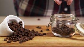 Chicco di caffè arrostito tiro dell'uomo dalla mano nel primo piano del barattolo con la borsa bianca vicino a 4K archivi video