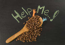 Chicco di caffè in cucchiaio di legno con aiuto me scrittura della mano immagine stock libera da diritti