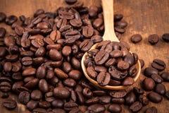 Chicco di caffè in cucchiaio di legno sulla tavola di legno Immagini Stock