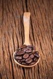 Chicco di caffè in cucchiaio di legno sulla tavola di legno Fotografia Stock