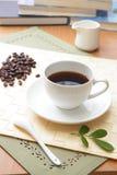 Chicco di caffè e caffè caldo con il foglio verde immagini stock libere da diritti