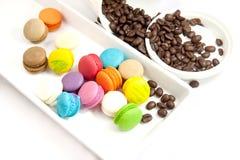 Chicco di caffè e mini maccherone variopinti in piatto caramic bianco Immagini Stock