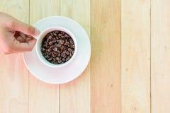 Chicco di caffè nella tazza sul piatto di legno fotografia stock libera da diritti