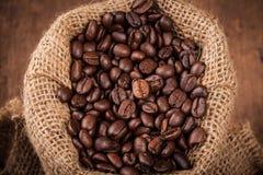 Chicco di caffè in sacco sulla tavola di legno Immagini Stock