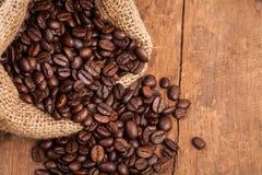 Chicco di caffè in sacco sulla tavola di legno Fotografia Stock Libera da Diritti