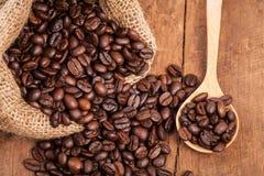 Chicco di caffè in sacco sulla tavola di legno con il cucchiaio di legno Fotografia Stock