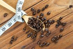 Chicco di caffè sul cucchiaio di legno, misura di nastro su fondo di legno Fotografie Stock Libere da Diritti