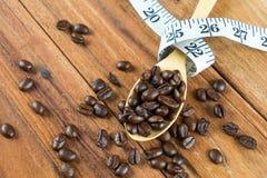 Chicco di caffè sul cucchiaio di legno, misura di nastro su fondo di legno Fotografia Stock Libera da Diritti